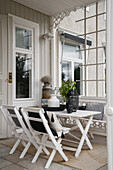 White wooden table with chairs on covered veranda