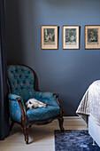 Blau gemusterter Sessel vor blauer Wand im Schlafzimmer