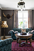 Sofa set, antique coffee table, floor lamp and antlers in the living room
