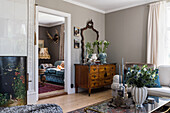 Antique chest of drawers and mirror in living room with grey walls