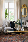 Antique glass table, upholstered sofa and gilt-framed mirror next to window in living room