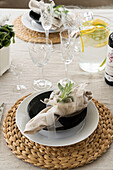 Festive place setting on round jute placemat, crystal glasses and pitcher of lemonade