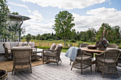 Rattan furniture on wooden terrace with landscape view