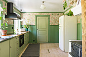 Green base units and nostalgic wallpaper in the kitchen