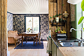View from the kitchen into the dining room with antique wooden table, sofa and wallpaper