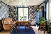 Antique wooden table, sofa and blue cabinet in dining room with patterned wallpaper