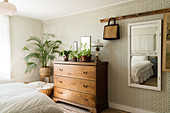 Wall mirror, wooden chest of drawers and indoor palm tree in the bedroom