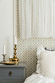 Bedside table with candlestick next to double bed in bedroom with nostalgic wallpaper and curtains