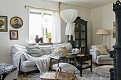 Cosy, rustic living room with upholstered furniture and glass cabinet