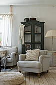 Grey upholstered armchair and glass cabinet in the cosy, rustic living room