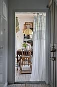 View through half-open door curtain to dining area
