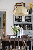 Wooden table below pendant lamp in rustic kitchen