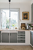 Kitchen with grey cupboard fronts in country-house style; window with garden view