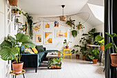 Many green plants, sofa and designer lamp in the living room