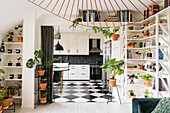 Shelves with houseplants and books next to and above the passage to the kitchen