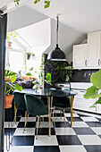 Table with black tabletop and upholstered chairs in the kitchen with chequerboard pattern floor