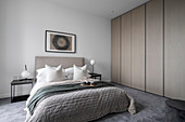 Modern bedroom in gray tones with a built-in wardrobe
