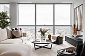 Modernes Wohnzimmer in gedeckten Farben mit Blick über die Stadt