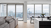 Open living room with large window offering a panoramic view of the city from a high-rise