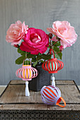 Handmade coloured paper lanterns hung from vase of roses
