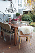 Terrace table decorated for autumn with chandelier, flowers in a basket planter, and sheepskin