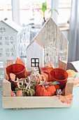 Autumn decorations with knitted pumpkins, lanterns, and wooden houses