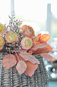 Bouquet of apricot ranunculus and sea lavender on artificial autumn leaves
