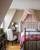 Canopy over metal bed in English-style bedroom