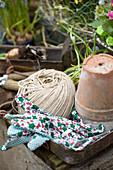 Still-life arrangement of terracotta pot, twine and work gloves