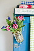 Tulips and grape hyacinths in suspended vase