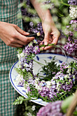 Woman tying wreath of lilac florets and tufted vetch