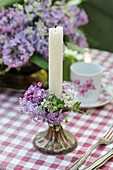 Wreath of lilac florets around candle