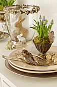 Easter decoration with grape hyacinths in silver cups, Easter eggs, birds, silver cutlery, and Easter bunnies