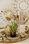 Easter decoration with grape hyacinths in a mug on a tray with silver cutlery, Easter eggs, and an hourglass