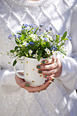 Frau hält Tasse mit Frühlingsstrauß aus Sternmiere und Vergißmeinnicht