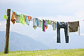 Laundry hung on washing line against blue sky and mountain panorama