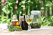 Different tinctures with herbs on garden table
