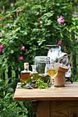 Verschiedene Tinkturen mit Kräutern auf Gartentisch