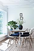 Klassikerstühle um Esstisch mit Gestell aus Schmiedeeisen und Eichenplatte