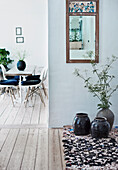 Floor vases on brocante carpet and vintage wall mirror