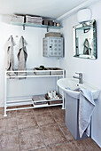 Washbasin, old potting table used as shelf and vintage wall-mounted cupboard in bathroom