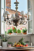 Ornate chandelier above plate of fruit on round antique table and potted plants in background