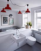 Weißes Badezimmer mit großem Wandspiegel und roten Pendelleuchten