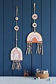 Handmade clay rainbow decorations hung on blue board wall