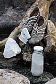 Training shoes, talcum powder and gauze bandage on piece of driftwood