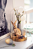 Gold-coloured Easter bunny and small bouquet of flowers under glass cover