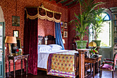 Antique double bed in the bedroom with red wallpaper