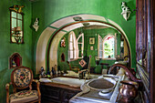 Antique armchair in green painted bathroom with round arch