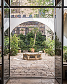 View through modern glass door into courtyard with fountain and plants