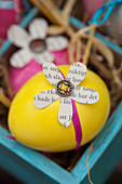 Newspaper flower decorating painted Easter egg